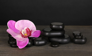 Spa stones with orchid flower on wooden table on grey