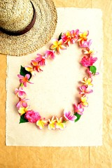 Lady's straw hat with plumeria lei