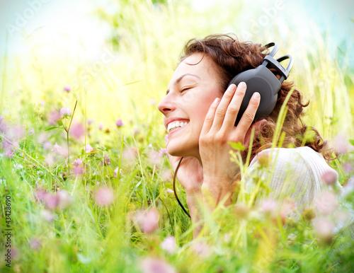 Leinwanddruck Bild Beautiful Young Woman with Headphones Outdoors. Enjoying Music