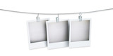 three blank polaroid pictures hanging on a wire isolated on whit