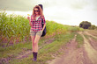 Young redhead woman with guitar passes corn field outdoors in su