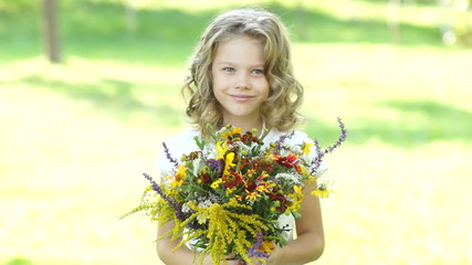 Preschooler girl with flowers outdoors