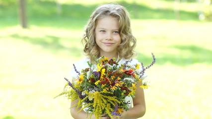 Preschooler girl with flowers outdoors
