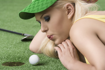 girl's playing with golf ball and hand under the chin