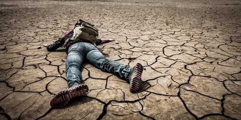 person lays on the dried ground