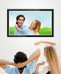 Young couple watching their photos on wide screen tv at home