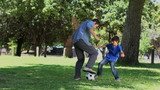 Son and his father playing football in a park