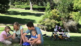 Family sitting while talking in a park