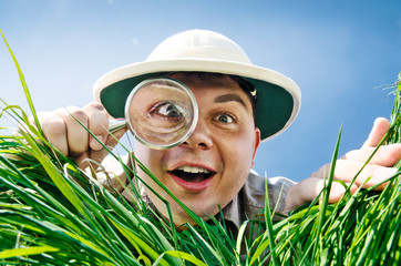 Young Man Looking through a Magnifying Glass