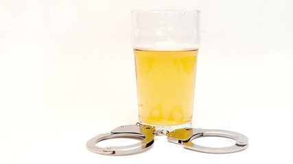 Car keys falling in a glass full of beer surrounded by cuff