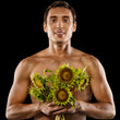 Sexy young muscular man with a bouquet of flowers in his hands