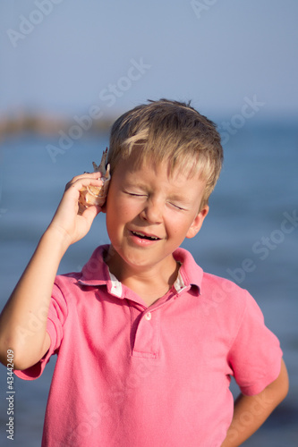 Child listens to a sea shell