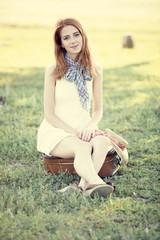 Redhead girl sitting at bag at outdoor.
