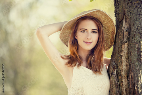 Redhead girl with hat near tree.