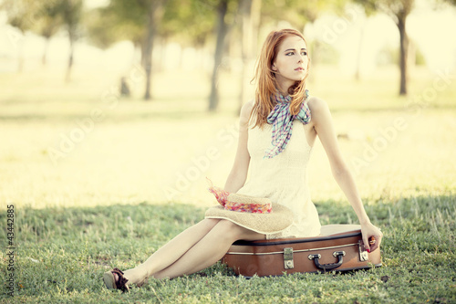 Redhead girl sitting at bag at outdoor.