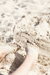 thins legs in the sand with cockleshellsc