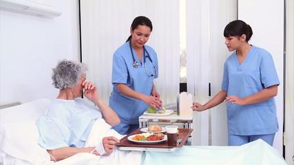 Nurse bringing food to a senior patient