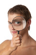 Cute young man looking through a magnifying glass