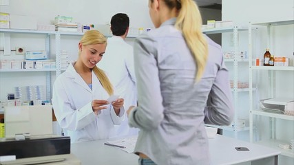 Someone giving a prescription to a pharmacist