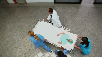 High angle view of a medical team pushing a patient on a bed