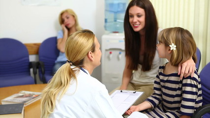 Female doctor talking to a girl in a waiting room