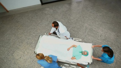 High angle view of a hospital team wheeling a patient on a bed