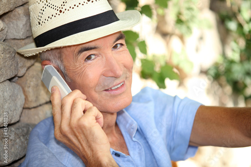Older man using a cell phone outdoors