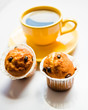 Coffee in an yellow cup and muffins