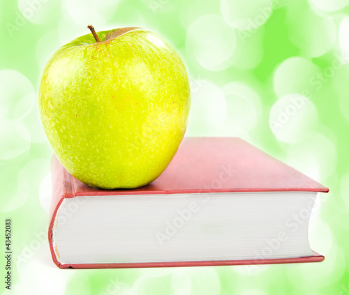 A green apple on a book