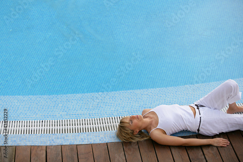 beautiful blonde resting on swimming pool edge