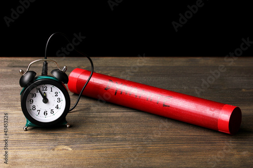 Dynamite with timer on wooden table on black background