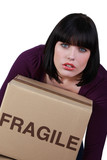Woman carrying a heavy box marked fragile