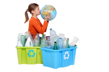 Girl recycling bottles and kissing a globe