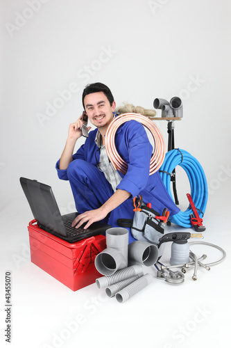 Labourer surrounded by tools and equipment