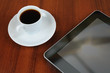 Cup of coffee and tablet pc on table
