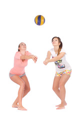 Young girls playing volleyball on white background