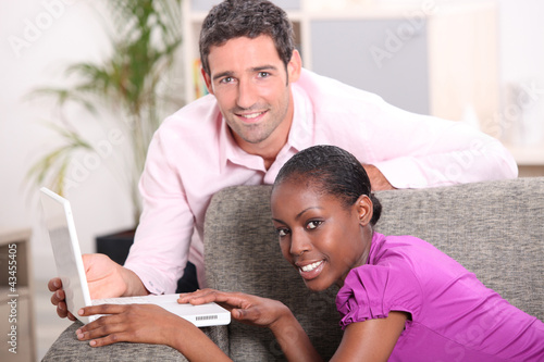Couple on gray sofa with computer