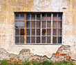 Large window with broken panes on dilapidated wall