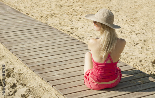 girl sitting back on track by the sea