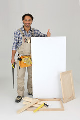 Woodworker stood with cabinet door and advertising panel