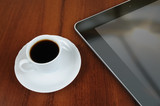 Cup of coffee and tablet pc on office table