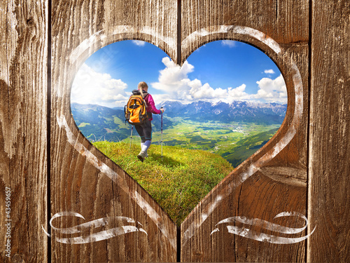 Woman hiking in wooden heart frame