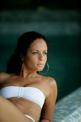 Woman in a bikini lying by a swimming pool