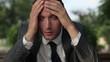 Portrait of  depressed businessman in the park, close up