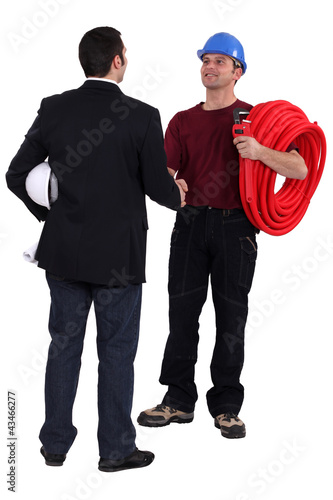 Architect shaking hands with a plumber