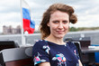 Portrait of young woman in dress with Russian flag on background