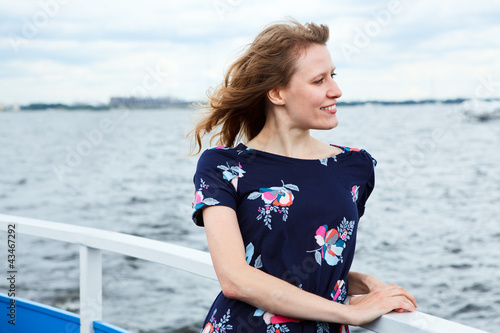 Girl standing on the deck of cruise yacht on wind and looking fa