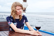 Pensive woman in dress with wine glass sitting at the table