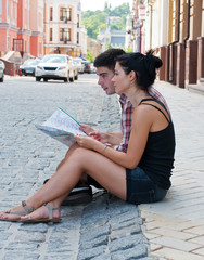 Girl and a guy sitting on the roadside with a map.