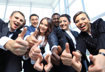 Happy multi-ethnic business team with thumbs up in